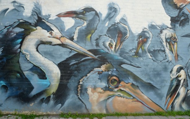 mural of many large birds in blues and greys, they all have long curved necks and large beaks