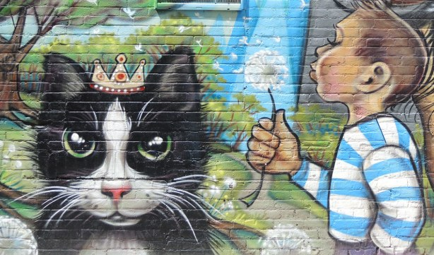 a large black and white cat is looking at the viewer.  It is wearing a little crown.  Beside the cat is a boy in a blue and white striped shirt who is blowing the seeds off a puffy white dandelion.