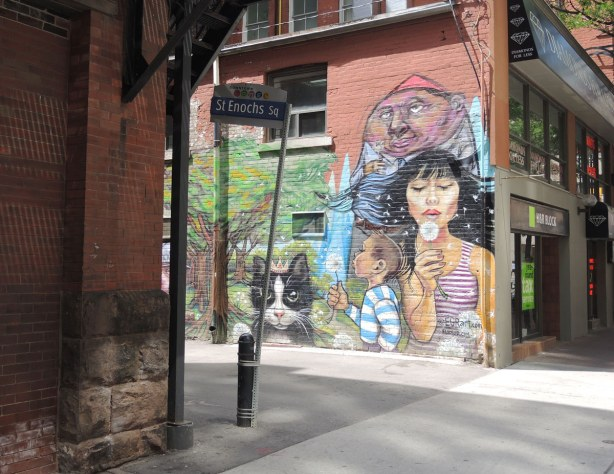 entrance to laneway, red brick building on the left (Massey Hall), mural painted on the wall on the right.  Mural shows a woman & a boy blowing the  seeds from white puffy dandelions.