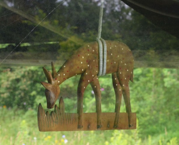 A little wooded sculpture of a deer eating grass is hung from the roof of the house with a piece of grey rope.  It is hanging by the back door.