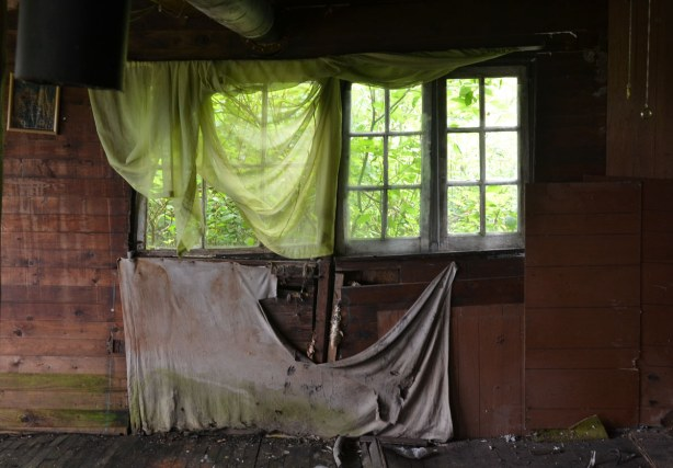 An empty living space, old wood walls that are showing signs of disrepair.  A window is in the wall, partly covered by an old light green flimsy curtain.  A dirty torn piece of grey fabric covers part of the wall below the wall.
