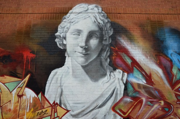 A street art painting of a bust of a woman, all white, looks like white marble Greek or Roman statue, very classical looking