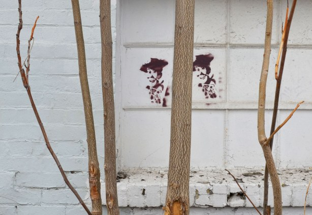 A few small trees are growing in front of an older building that has been painted white.  Two brown figures have been stencilled onto the wall.
