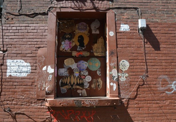brown brick wall with a window that has been boarded over and painted the same brown colour.  In the window, and on the window frame, are a large number of sticker graffiti pieces.