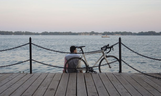 A cyclist and his bike are sitting at the edge of Lake Ontario, behind the chain fence.  It is evening and the sky is strating to turn pink