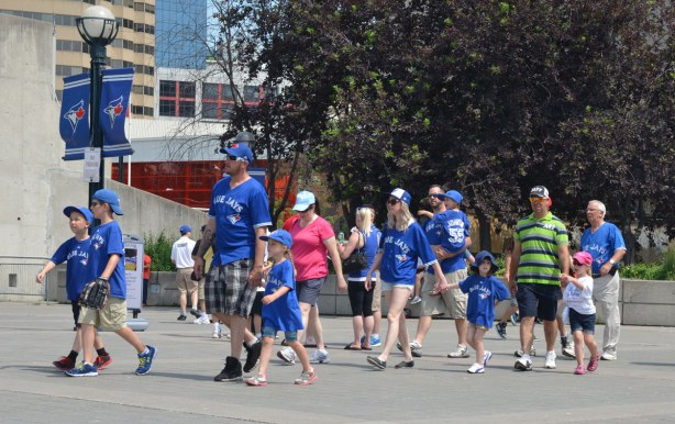 A large group of people, inlcuding many kids, are walking towards Rogers Stadium for a Blue Jays baseball game.  Most of them are wearing blue Blue Jays shirts.