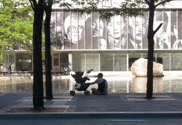A man is sitting beside a stroller in the foreground.  Behind him is a pool of water and then a large glass building.   On the wall of the building are black and white images of some famous people including Andy Warhol, JFK, and Albert Einstein