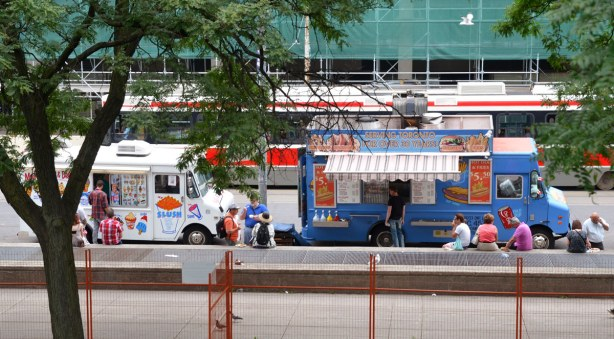 Two food trucks are parked on the street.  People are buying food, or sitting on the conrete bench (low wall) that runs parallel to the sidewalk