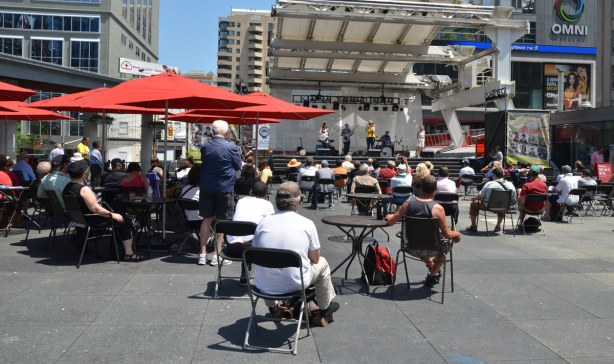 Dundas Square with many people sitting on chairs, under red umbrellas, watching a band play on stage
