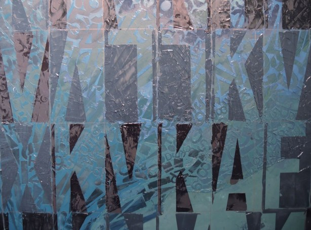 Painting of letters upside down and rightside up in greys and blues.