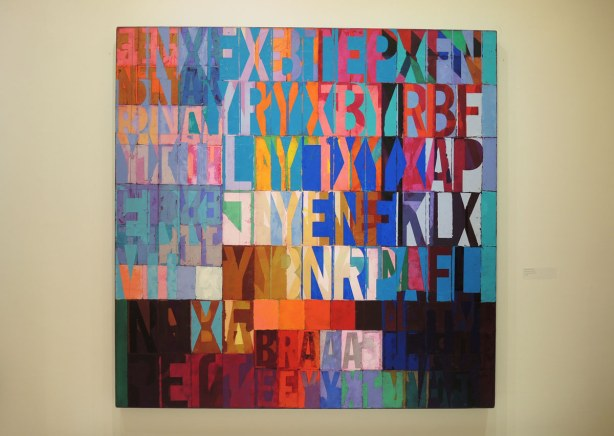 a very colourful painting that looks like a mosaic of diffferent coloured letters on different coloured squares and rectangles.