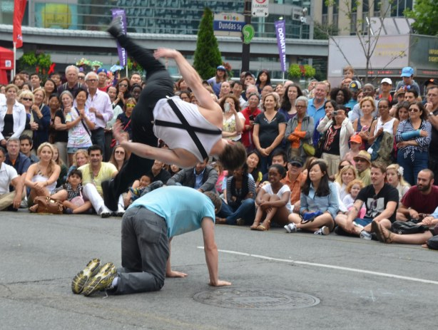 One of the street performers from the group Touch2Catch is doing a side flip over a man who is on all fours on the street.