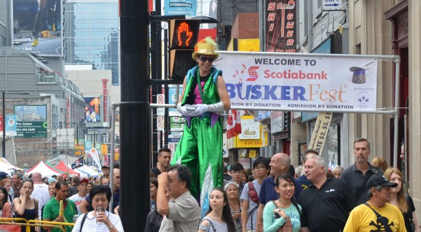 A man dressed in green is on stilts as he walks up Yonge St.