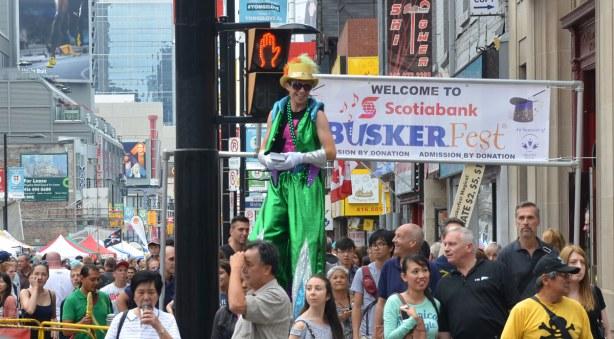A man dressed in green is on stilts as he walks up Yonge St.