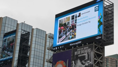A large electronic billboard high above Yonge St.  A picture of one of my buskerfest tweets is being displayed.
