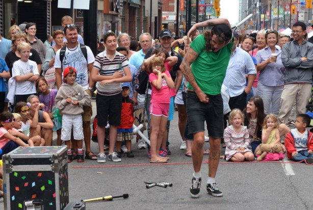 A street performer is twisting the upper part of his body in order to fit it through a tennis racquet.