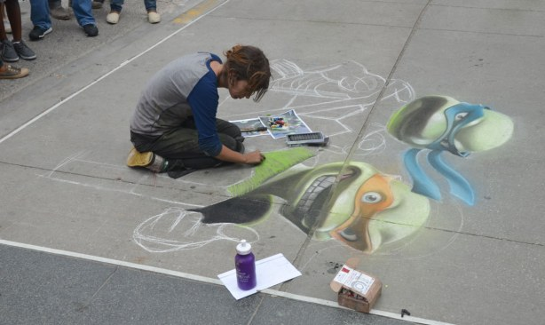 A woman is using chalk to make a large picture of the Teenage Mutant Ninja Turtles on the sidewalk