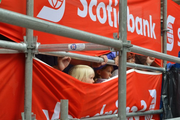 Some children are watching buskers perform by peeking through a gap in the red and white plastic banners that are the backdrop to the show.
