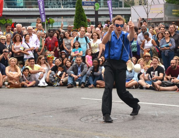 A street performer is using a diabolo to entertain a crowd of people who are sitting and standing on the sidewalk around him.