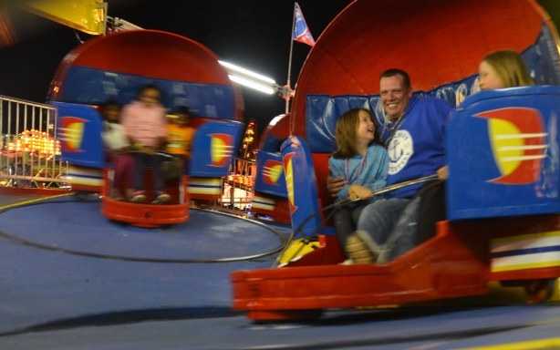 "A father and his daughters are on a midway ride, spinning in red ""seats"" as they go around in circles."
