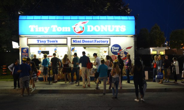 Evening shot as the sky is getting darker.  Tiny Tom donut stand all lit up, with a line up of people waiting to buy donuts.