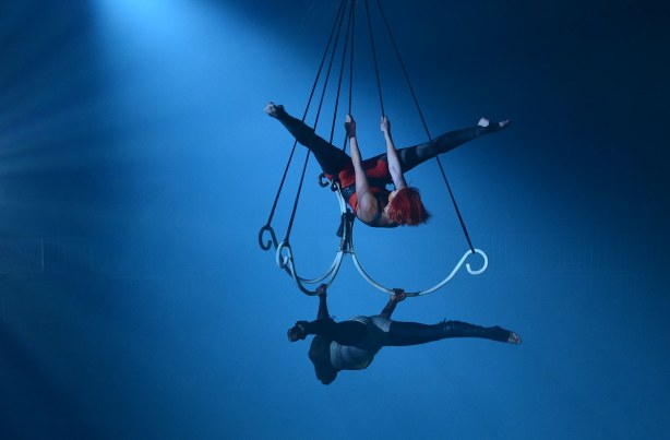 Two acrobatic women hanging from a large triple hook shaped bar suspended from the ceiling.  Bathed in blue light.