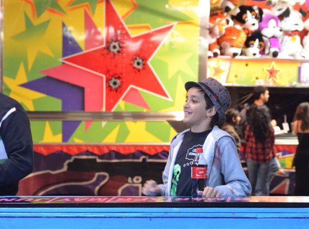 A boy wearing a fedora is standing beside one of the midway games.  He is holding a coke bottle with the name Jeff on it.  Behind him is a large picture of 3 stars.