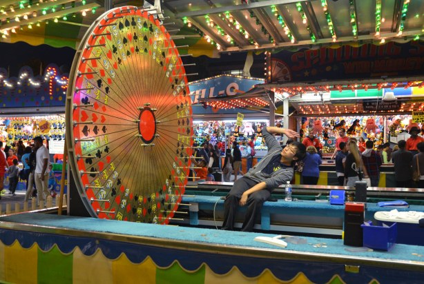 A young man is sitting by a giant roulette wheel, a midway game at the Ex