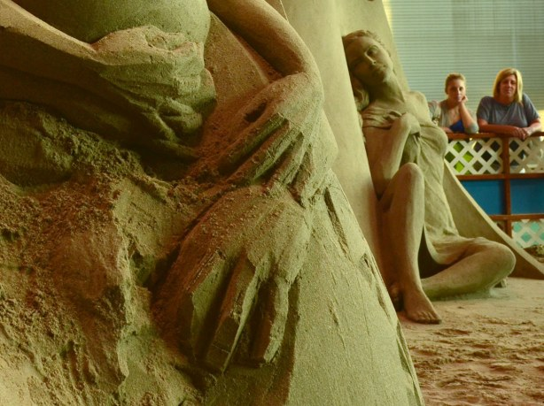 Details of a sand sculpture (hands) with another sculpture behind (of a woman)