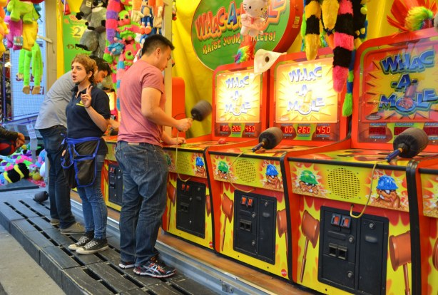 Two young men are hammering away at Whac-a-mole while a woman who is running the game is talking to the people who are watching