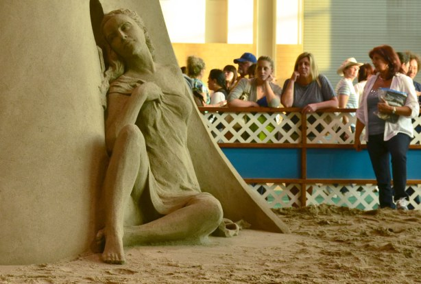 Sand sculpture of a woman sitting on the ground, looking wistfully through a round window.  In the background are some woman standing behind a wood barricade who are looking at the sand sculpture