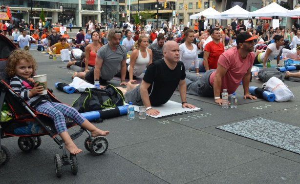 Group of people at Dundas Square doing yoga postures as part of a yogathon.  A young girl sits in a stroller with a Starbucks cup in her hand.  She is watching the yoga (but smiling at the camera)