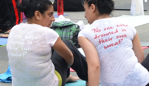 Two women are sitting on the ground and talking to each other.   Their backs are to the camera.  On the back of their Tshirts are the words 'no one ever drowned in their own sweat'.