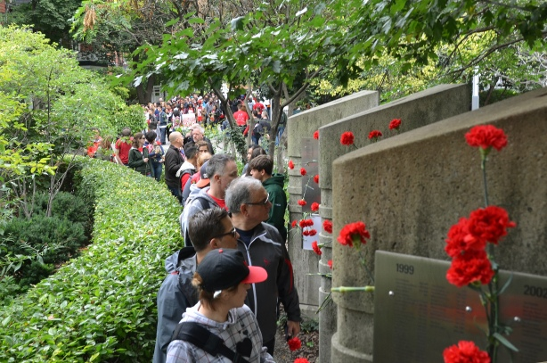 A group of people is winding its way through a park in which there are short concrete pillars.  Each pillar has plaques on it with the names of the people from Toronto who have died of AIDS.  Red carnations have been placed by the plaques O