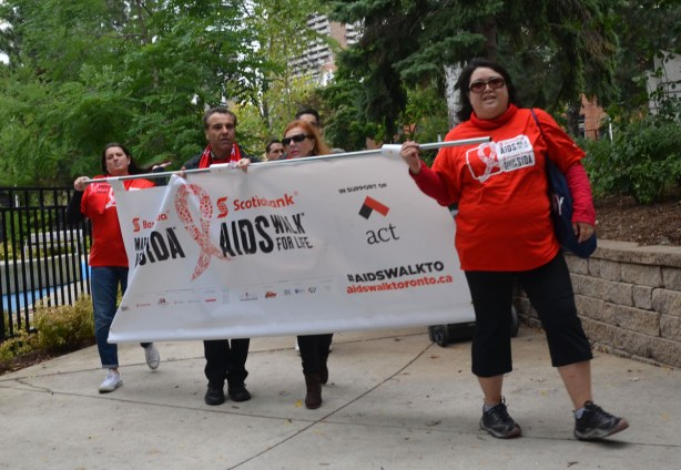 A small group of people is holding a banner in the walk.  The banner says Scotiabank AIDS Walk, in support of ACT .  A C T is AIDS committee Toronto.