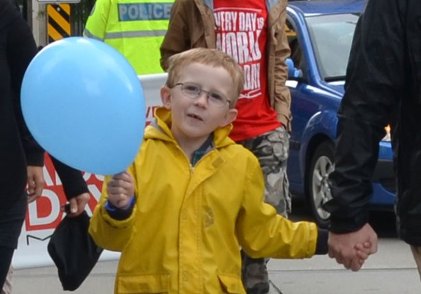 people at the AIDS walk in Toronto.  A boy in a yellow raincoat and holding a blue ballon is smiling for the camera.