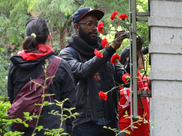 people at the AIDS walk in Toronto.  A man is putting a red carnation on the AIDS Memorial in Toronto.  Quite a few carnations are already there.