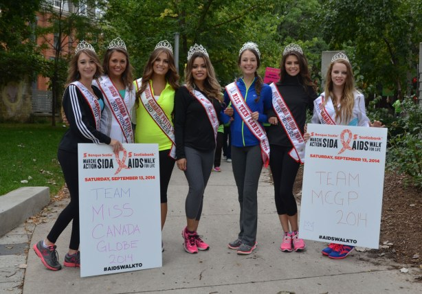 people at the AIDS walk in Toronto.  Miss Teen Canada winners, seven of them, are walking as a group.  They have stopped to have their photo taken.