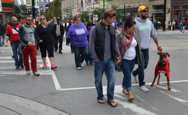 people at the AIDS walk in Toronto, walking up YOnge St.  One man has a dog on a leash.  The dog is wearing a red Tshirt.