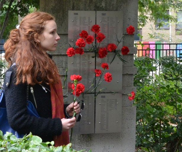 A young woman is holding a red carnation as she waits her turn to lay it with the others at the AIDS memorial.  One of the triangular pillars with 6 plaques on it is behind her.