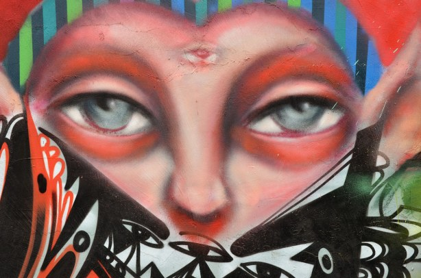 Colourful graffiti in a Kensington lane.  Close up of a pair of grey eyes.  Bottom part of face is obscured, including her cheeks.