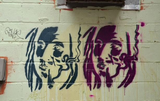 Colourful graffiti in a Kensington lane stencils of heads, one dark blue and one purple.