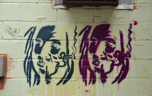 Colourful graffiti in a Kensington lane stencils of heads, one dark blue and one purple.