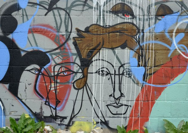 Street art painting on the side of a brick wall, black line drawn faces with some reds, whites and blues , and one with brown hair