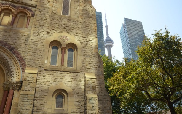 Part of the stone church, St. Andrews Presbyterian, dominates the photo.  Part of a tree, the edge of a skyscraper and the CN Tower are on the right side of the photo.
