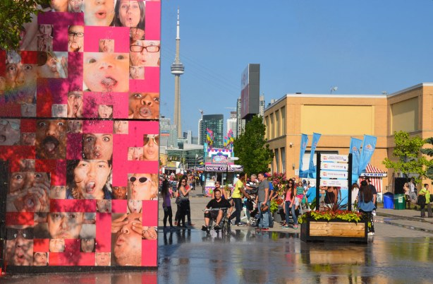 The pink wall of faces is a fountain and it is on the left side of the photo.  People at the ex and the CN Tower are also in the photo.