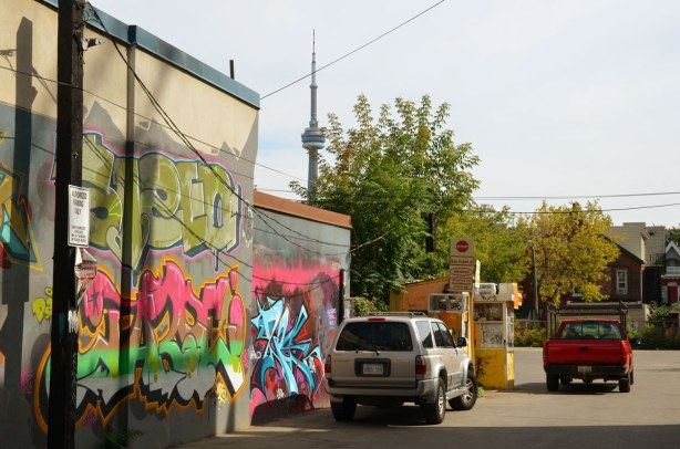 An SUV and a red truck are parked in a parking lot.  On the left side of the picture are two walls that are covered with graffiti.  The CN Tower is above one of those walls.