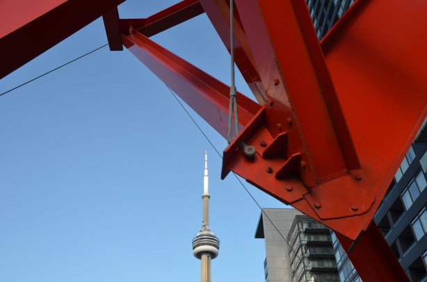 Part of a bright red metal sculpture is in the foreground.  The CN tower is in the background (the top part of it anyhow)