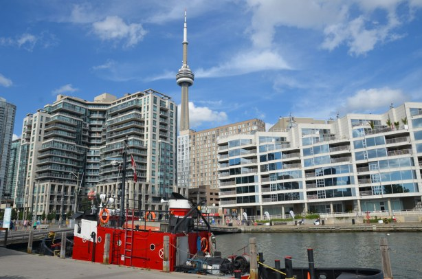 A bright red tugboat is tied up in the foreground.  Many glass windows of many condos are in the photo.  The top of the CN tower is peaking up over the top of the condos on Toronto's waterfront.