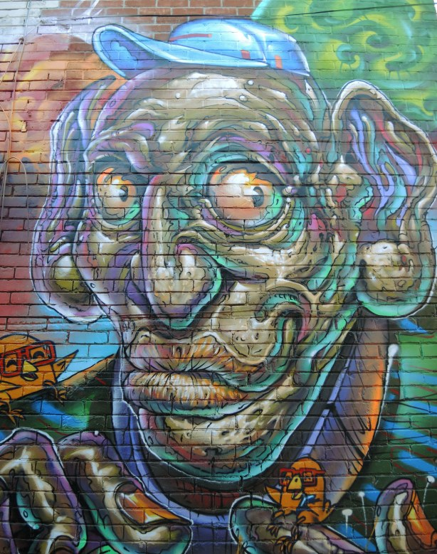 part of a large mural, a very large wrinkly man's face with large eyeballs and large ears